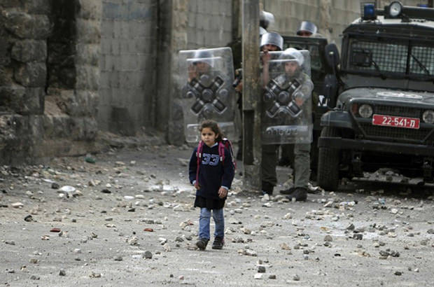 A young girl, unconcerned by the violence around her, makes her way to school past Israeli troops with protective shields.