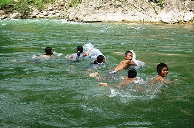 Children between grade 1 and 5 swim across this 20 meter deep river to get to school at the Trong Hoa commune