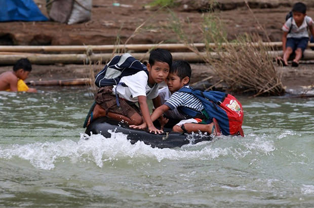 Elementary school students of this remote village make a river crossing on inflated tire tubes