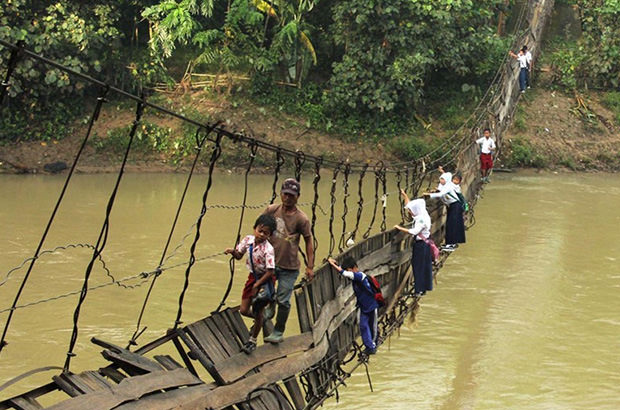 To get to school, children from the village of Sanghiang Tanjung traverse the Ciberang River via this collapsed suspension bridge