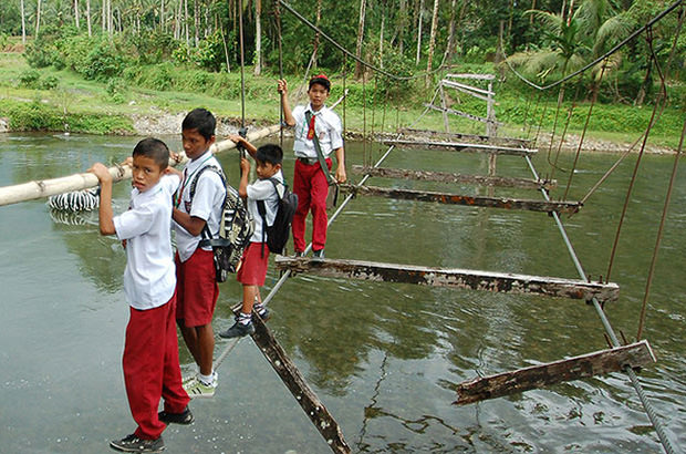 School children cross this bridge that was stripped bare following an earthquake