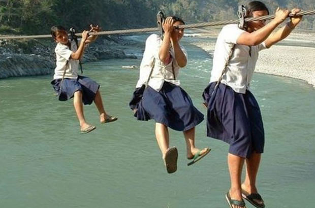 School children in Nepal use makeshift ropes and pulleys to get across ravines to get to school